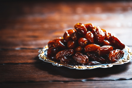 Islamic Dried dates on a traditional tray on a wooden background. Ramadan Kareem concept.Three months. Stock Photo