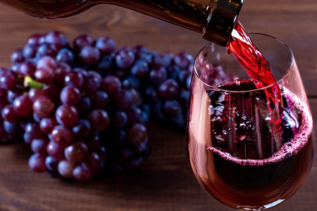 Bottle and glass of red wine, grape and cork on wooden background