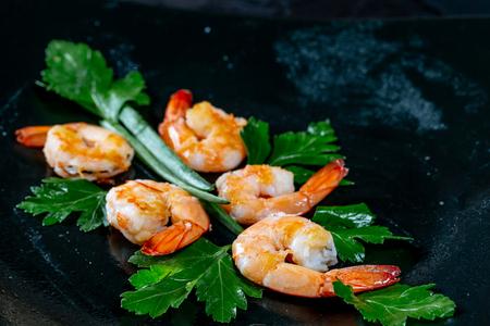 Fresh peeled grilled shrimp with herbs on black background. Flatley. Food background a gourmet meal Standard-Bild