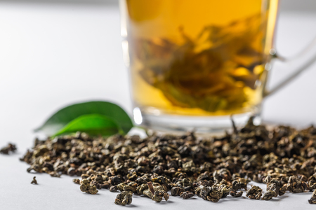 A Cup of green tea with dried large leaf tea and fresh tea leaves on a white background. Diet and healthy drink
