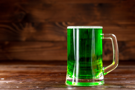 Glass mug with green beer on a rustic wooden surface. Festive background for St. Patrick's day. Free space