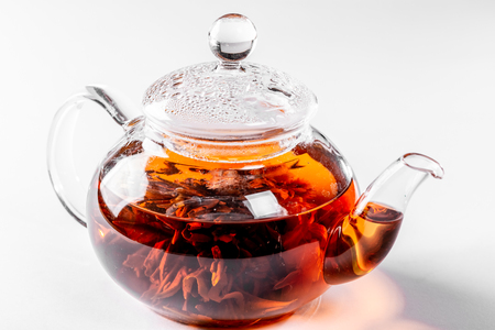Tea in a glass teapot with a blooming large flower. Teapot with exotic green tea on white background