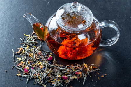 Tea in a glass teapot with a blooming large flower. Teapot with exotic green tea-balls blooms flower and dried tea and rose buds