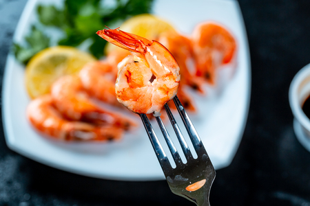 Grilled prawns on fork, behind soy sauce, lemon and herbs. Royal delicious and beautiful peeled shrimp. Flatley. Food background on black stone
