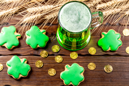 Green beer in a glass mug with gingerbread clover, horseshoe, wheat spike and gold coins on a rustic wooden surface. Festive background for St. Patrick's day.