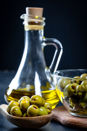 Olive oil in vintage glass bottles with green olives in wooden spoon on black background. Copyspace. Flatley. Food background with water drops.Healthy eating and diet concept