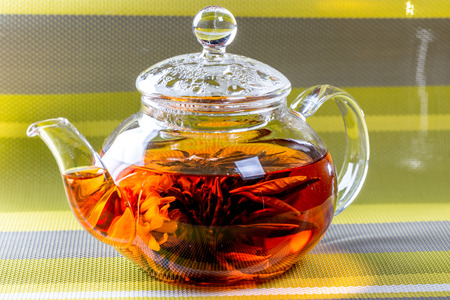 Tea in a glass teapot with a blooming large flower. Teapot with exotic green tea-balls blooms flower. Tea ceremony on green striped background Standard-Bild