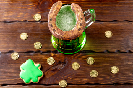 Green beer in a glass mug with gingerbread clover, horseshoe and gold coins on a rustic wooden surface. Festive background for St. Patrick's day. Standard-Bild
