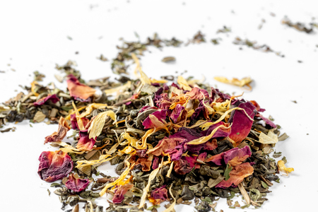 Green tea with dried flower petals and pieces of citrus on white background. Dried tea for welding. Diet and healthy drink