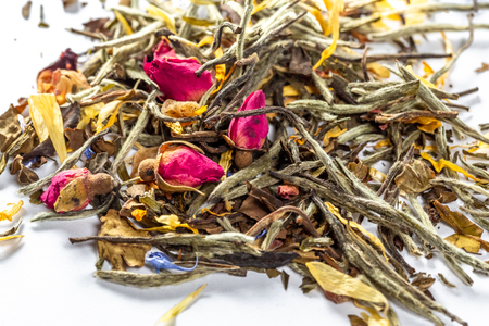 White tea with flowers, petals and rosebuds on white background. Close up of chinese white tea of premium luxury quality. Texture background macro photo. Bai Hao Yinzhen tea.