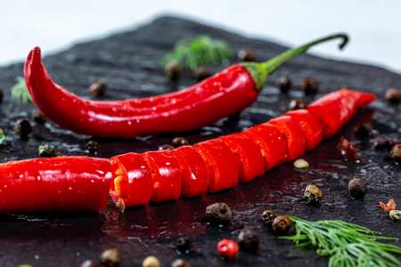 Fresh chili Pepper spicy with spices and herbs on black stone background. The concept of cooking food, the ingredients of the dish. The view from the top. Flatley