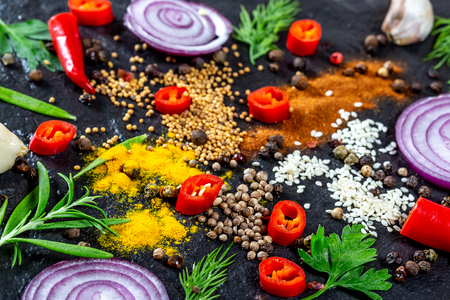 Different kind of spices and herbs, chili, garlic and onion on a black stone background