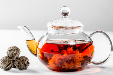 Tea in a glass teapot with a blooming large flower. Teapot with exotic green tea on a white background with dried balls-buds for tea brewing Standard-Bild