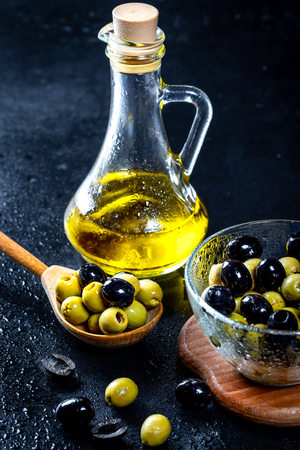 Olive oil in vintage glass bottles with black, green olives and wooden spoon on black background. Copyspace. Flatley. Food background with water drops.Healthy eating and diet concept