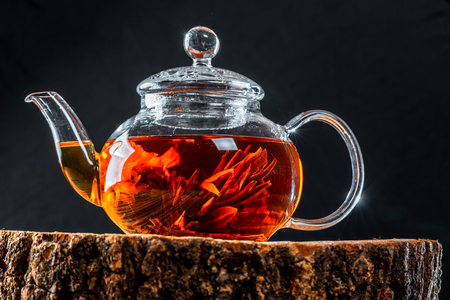 Tea in a glass teapot with a blooming large flower. Teapot with exotic green tea-balls blooms flower. Tea ceremony on a wooden stump Standard-Bild
