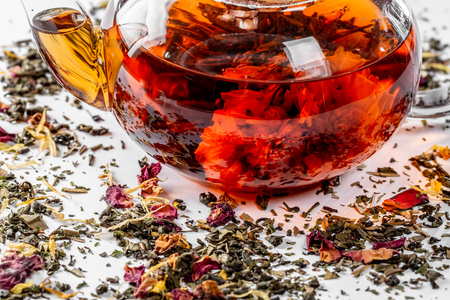 Tea in a glass teapot with a blooming large flower. Teapot with exotic green tea on a white background with scattered dried tea with petals and pieces of fruit Standard-Bild