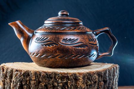 Ceramic teapot on a wooden stump. Tea ceremony