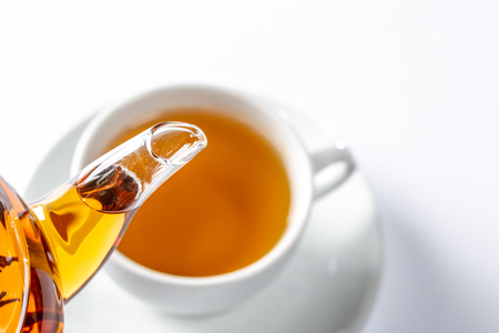 From a glass teapot poured tea into a Cup. Teapot with exotic green tea. Tea ceremony
