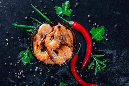 Grilled prawns with chili pepper. Royal delicious and beautiful shrimp. Flatley. Food background on black stone
