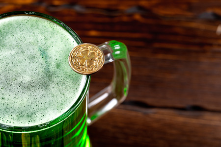 Green beer in a glass mug with gold coins on a rustic wooden surface. Festive background for St. Patrick's day. Free space