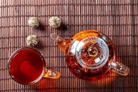 Tea in a glass teapot with a blooming large flower. Teapot with exotic green tea-balls blooms flower and a glass Cup of tea. Tea ceremony on a dark background Standard-Bild