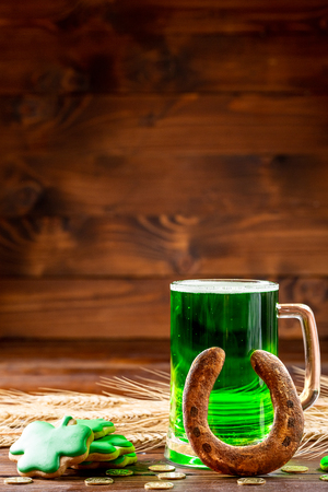 Green beer in a glass mug with gingerbread clover, horseshoe and gold coins on a rustic wooden surface. Festive background for St. Patrick's day with wheat ears. Free space Standard-Bild