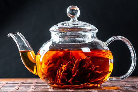 Tea in a glass teapot with a blooming large flower. Teapot with exotic green tea-balls blooms flower. Tea ceremony on a dark background