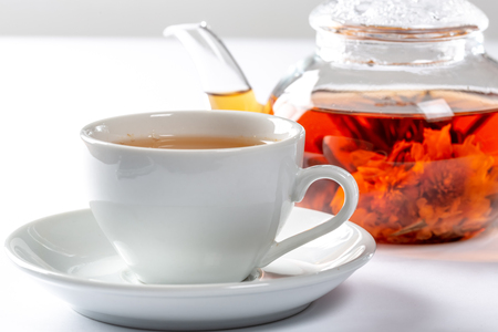 A Cup of fresh tea on a saucer, behind the Tea in a glass teapot with a blooming large flower. Exotic green tea on white background