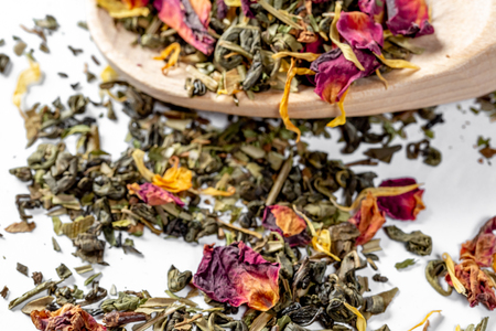 Green tea with dried flower petals and pieces of citrus on a wooden spoon. Dried tea for welding. Diet and healthy drink