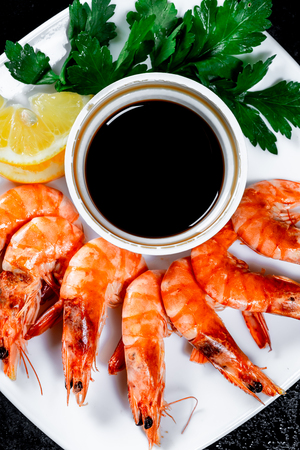 Grilled prawns with soy sauce, lemon and herbs. Royal delicious and beautiful shrimp on black background. Flatley. Food background