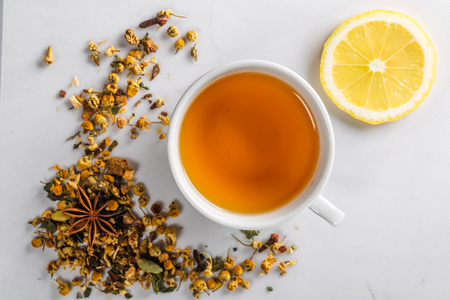 A Cup of green tea with dried chamomile flowers and a slice of cut lemon on a white background. Diet and healthy drink. Flatley. Top view Standard-Bild