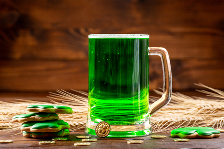 a glass mug with dyed green beer on a rustic wooden surface