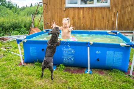 The child swims in the country pool with a French bulldog. Hes playing squirt with a dog.