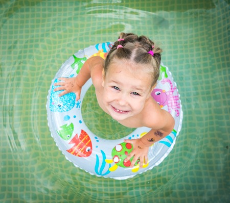 The child swims on an inflatable circle.