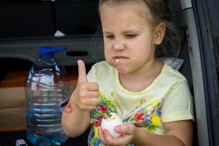 Little girl Beautiful blonde girl eating a boiled egg.