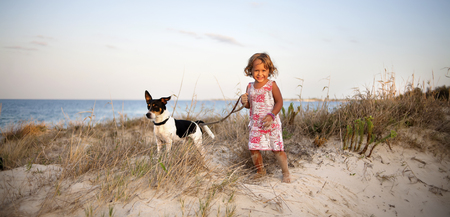 Foto panorâmica de dois anos de idade menina rindo exploração Jack Russell cachorro na coleira na praia Foto de archivo
