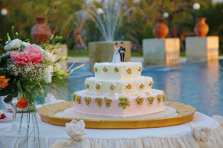 Wedding cake with the decoration of the bride and groom on top on the background of the pool
