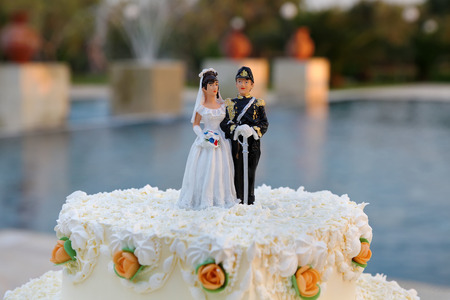 Wedding cake with the decoration of the bride and groom on top closeup view