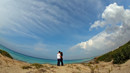 A loving couple is hugging on the seashore panoramic Stock fotó