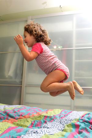 pequeña niña feliz está saltando en la cama Foto de archivo