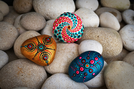 Beautiful hand painted mandala stones lies on the rocks Archivio Fotografico