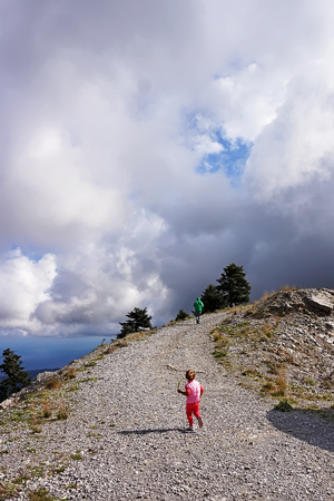 little girl climbs the mountain road in Evia, Greece