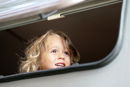 the little girl looks out happy of the camper window Stock Photo