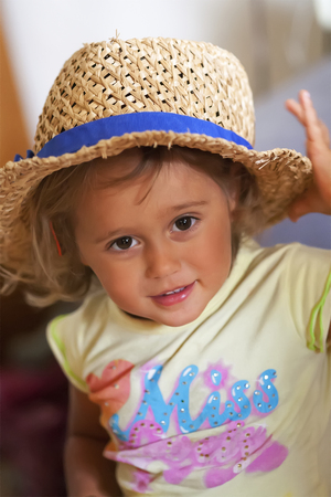 Happy Little girl 2-3 years old in hat looking in camera