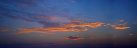 Beautiful sky with orange clouds at sunset with airliner