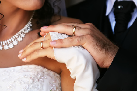 hands of the bride and groom with wedding rings closeup