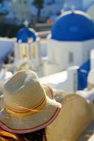 Woman with a hat on the background of Oia, Santorini