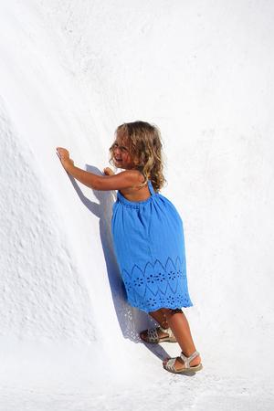 Beautiful blonde baby girl posing as a model by a small church of Oia in Santorini, Greece Banco de Imagens