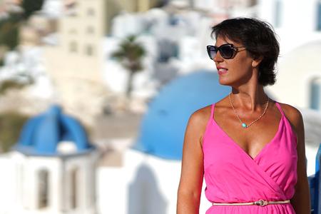 Woman with Fuchsia dress admires the Oia Scenery in Santorini, Greece