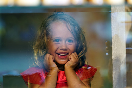 Beautiful little girl looks in the window of a shop in OIA, and makes many funny faces
